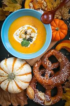 Тыквенный суп. сезонные блюда. суп украшен тыквенными листьями и кренделями. осень