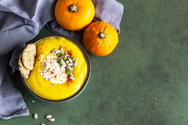 Pumpkin soup served in a bowl with cream, seeds and multigrain crackers.