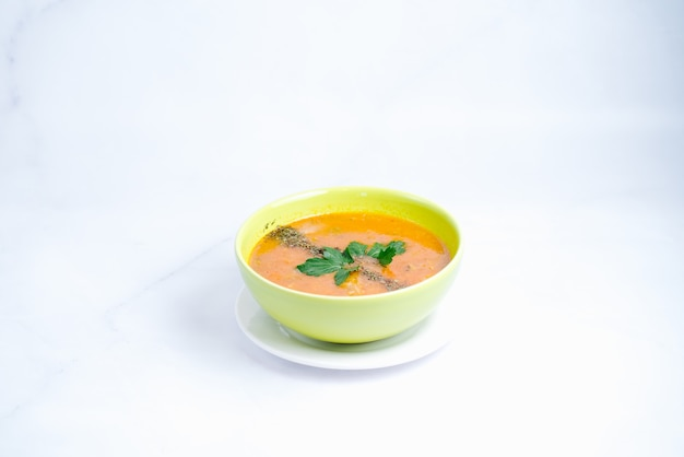 Pumpkin soup topped with pepper and herbs