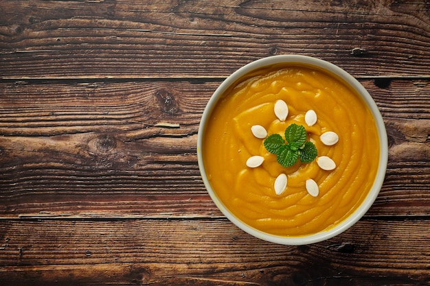 Zuppa di zucca in una ciotola bianca posta sul pavimento di legno
