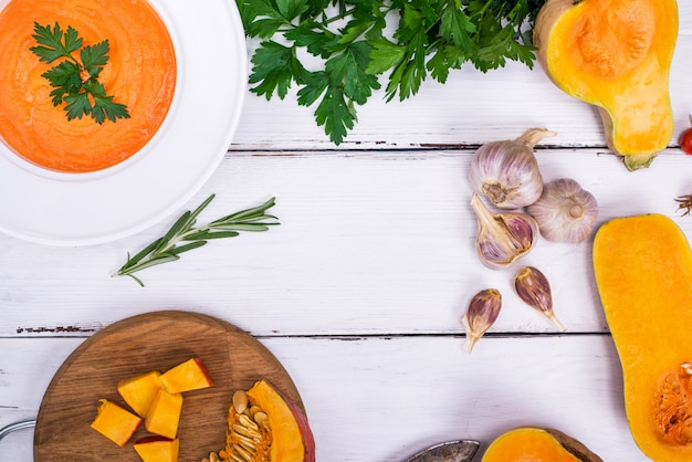 Pumpkin soup in a white plate and ingredients