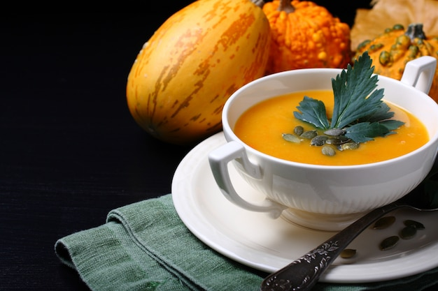 Pumpkin soup in white plate with celery leaves  on black