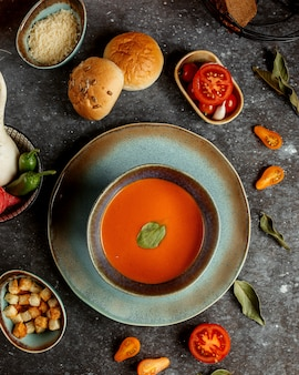 Pumpkin soup with buns and sliced tomato