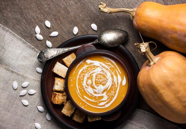Тыквенный суп со сливками и кунжутом в коричневой керамической миске