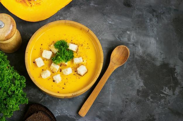 그런 지 블랙 테이블 위에 소박한 금속 접시에 크림, 빵, 신선한 파 슬 리와 호박 수프. 상위 뷰, 복사 공간.