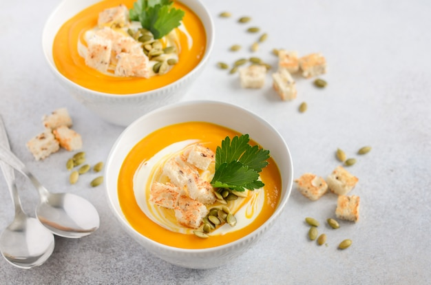 Pumpkin soup with cream, croutons, pumpkin seeds and parsley on a gray concrete or stone.