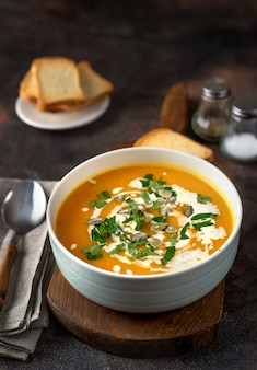 Pumpkin soup with cream and parsley on dark rustic table