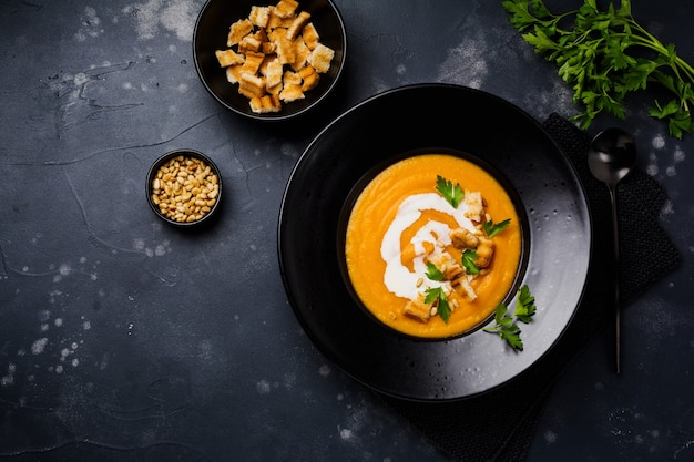 Тыквенный суп со сливками, кусочками хлеба и кедровыми орехами в черной керамической тарелке на темной деревянной поверхности. традиционная осенняя еда. копирование пространства вид сверху.