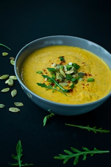 Pumpkin soup with cream and pumpkin seeds, served in a light bowl