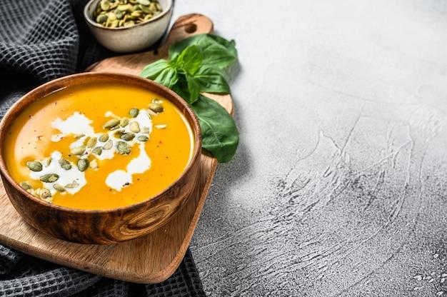 Тыквенный суп со сливками, семенами и свежим базиликом в деревенской деревянной миске. серый фон