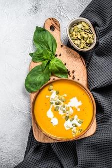 Тыквенный суп со сливками, семенами и свежим базиликом в деревенской деревянной миске
