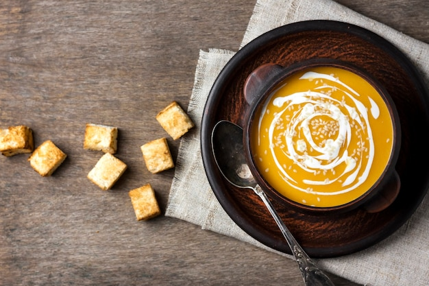 Pumpkin soup with cream and sesame seeds in brown ceramic bowl on wooden surface