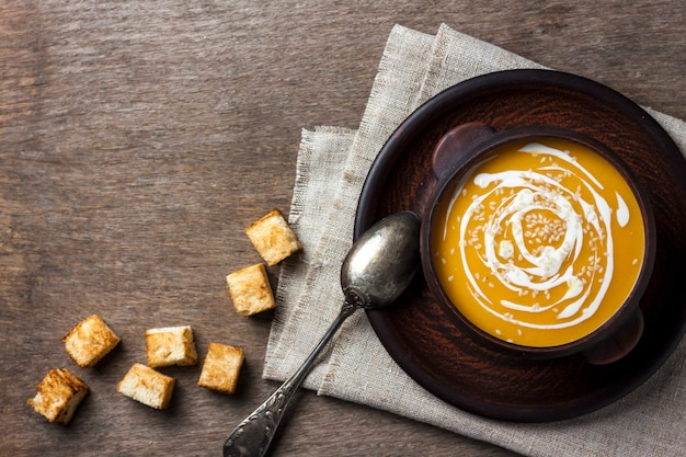 Pumpkin soup with cream and sesame seeds in brown ceramic bowl