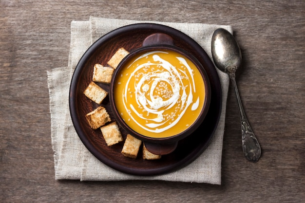 Pumpkin soup with cream and sesame seeds with croutons on wooden background