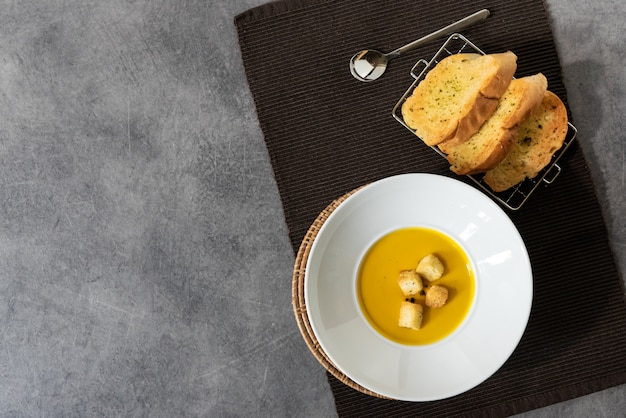 Pumpkin soup with croutons bread in plate garlic bread on stone background with blank copyspace
