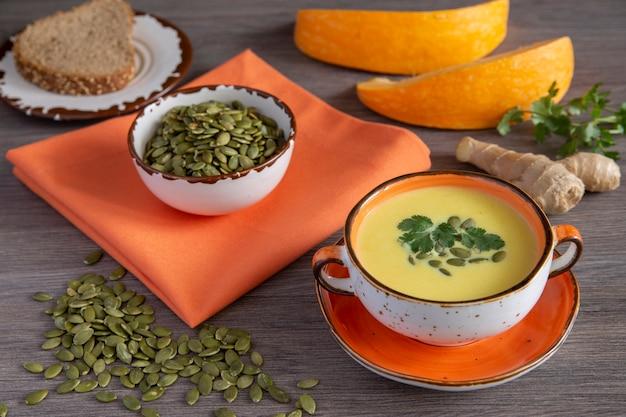 Тыквенный суп с имбирем и тыквенными семечками горячий осенний суп на фоне деревянного стола