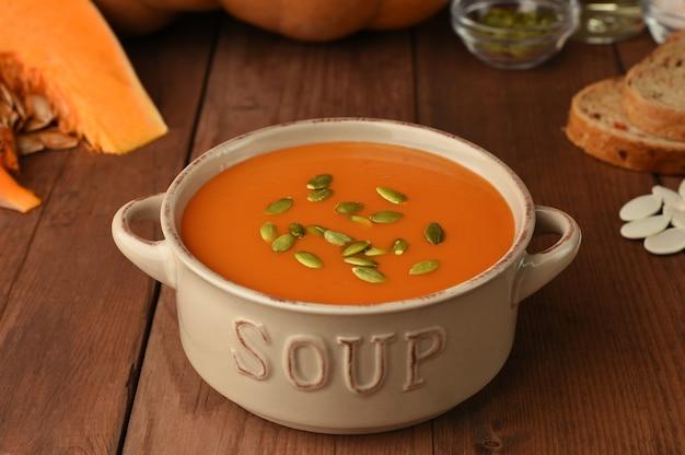 素朴な木製のテーブルの食材を使ったカボチャのスープ。自家製秋スカッシュスープの周りの熟したカボチャ、パン、油、種子のスライス。メニュー、レシピ。