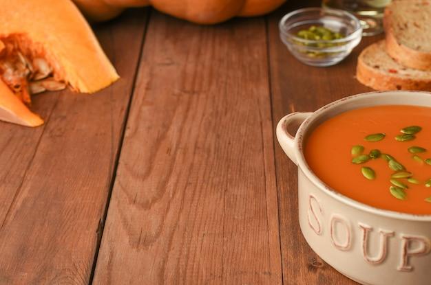 素朴な木製のテーブルの食材を使ったカボチャのスープ。熟したカボチャ、パン、油、種子のスライス。コピースペースを持つ木製の秋の食べ物の背景。