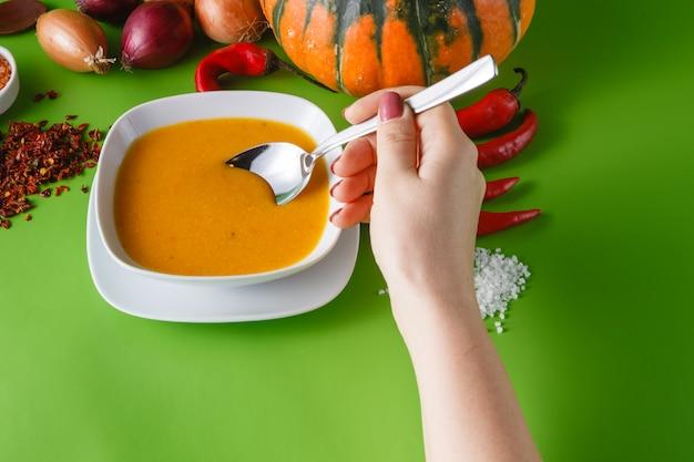 Тыквенный суп с луком и перцем на зеленом фоне без тени
