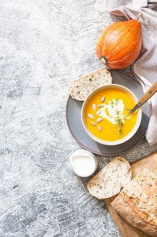 Pumpkin soup with pumpkin seeds, crisp bread and thyme with  copyspace