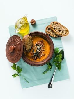 種とテーブルの上の粘土ボウルでライ麦パンのパンプキンスープ
