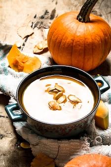 Тыквенный суп с семенами на старой ткани. на деревянном фоне.
