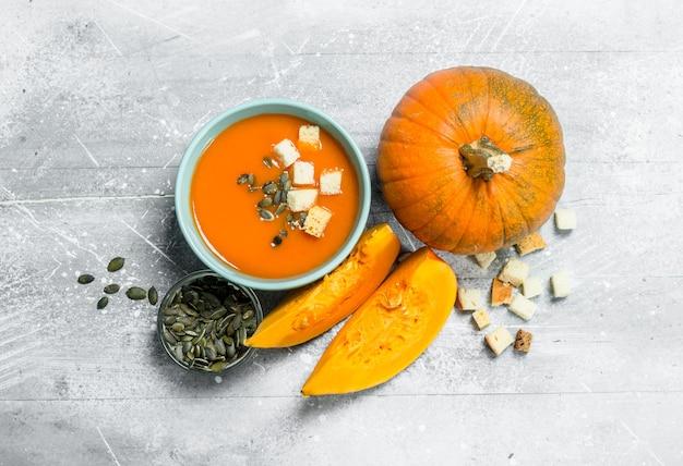 Тыквенный суп с кусочками спелой тыквы и семечками. на белом деревенском фоне