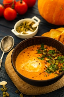 Pumpkin soup with sour cream and pumpkin seeds on a wooden table.