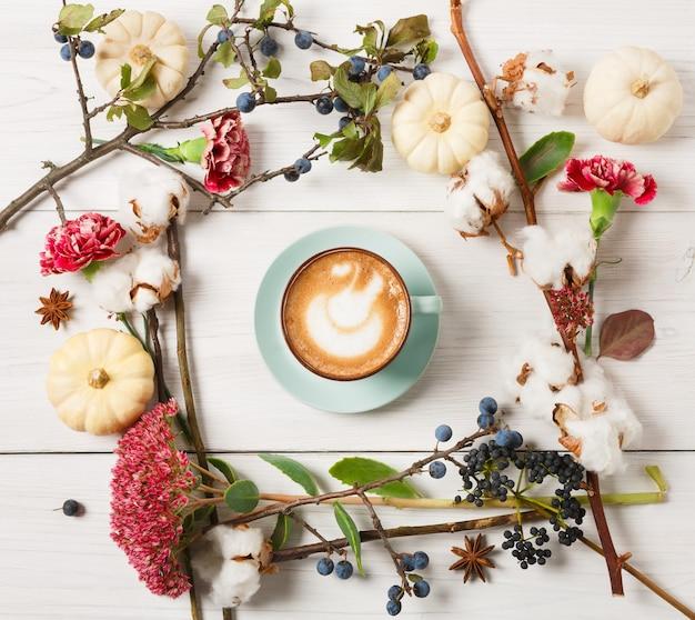 パンプキンスパイスラテ。クリーミーな泡、秋のドライフラワー、スロー、小さな黄色のカボチャ、上面と青いコーヒーカップ。秋のホットドリンク、季節のオファーのコンセプト
