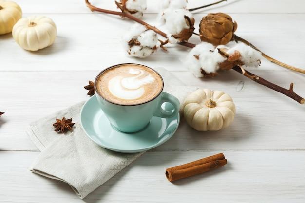 パンプキンスパイスラテ。クリーミーな泡、シナモンスティック、小さな黄色のカボチャが入った青いコーヒーカップ。秋のホットドリンク、カフェ、バーのコンセプト