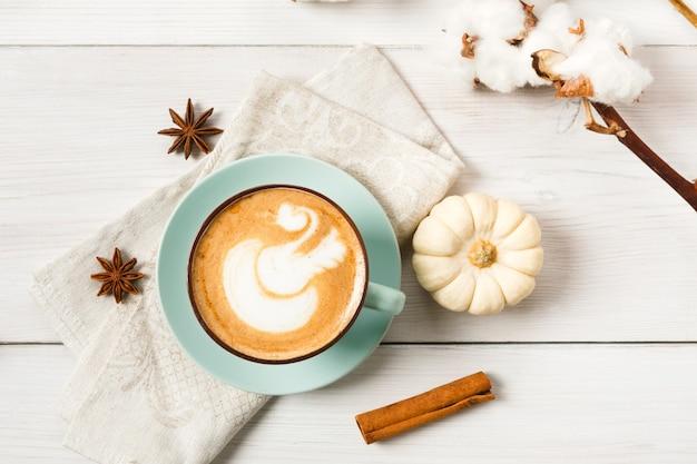 パンプキンスパイスラテ。クリーミーな泡、シナモンスティック、アニス、小さな黄色のカボチャが入った青いコーヒーカップ。秋の秋のホットドリンク、カフェ、バーのコンセプト、トップビュー