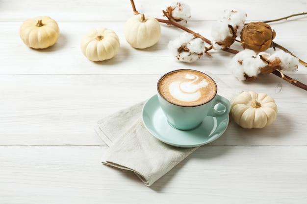 Латте со специями из тыквы. синяя кофейная чашка со сливочной пеной, палочками корицы, осенним терном и маленькими желтыми тыквами. осенние горячие напитки, концепция кафе и бара