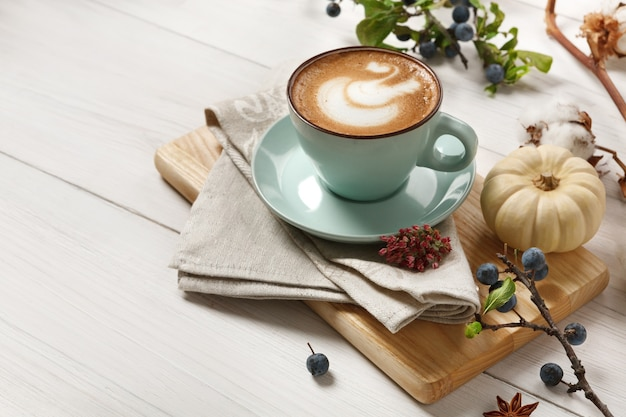 Pumpkin spice latte. blue coffee cup with creamy foam, cinnamon sticks, autumn sloe and small yellow pumpkins. fall hot drinks, cafe and bar concept