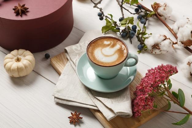 パンプキンスパイスラテ。机の上のクリーミーな泡、秋のドライフラワー、スロー、小さな黄色のカボチャと青いコーヒーカップ。秋のホットドリンク、季節のオファーのコンセプト