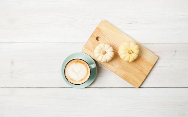 パンプキンスパイスラテ。泡と小さな黄色のカボチャと青いコーヒーカップ。秋の秋のホットドリンク、カフェ、バーのコンセプト、トップビュー