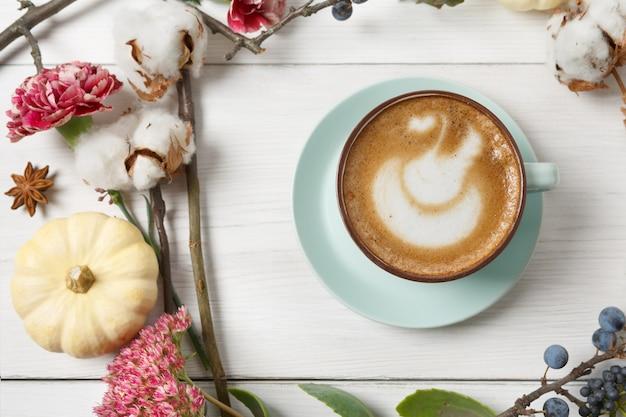 パンプキンスパイスラテ。泡、シナモンスティック、秋の花、小さな黄色のカボチャと青いコーヒーカップ。秋のホットドリンク、カフェ、バーのコンセプト、トップビュー