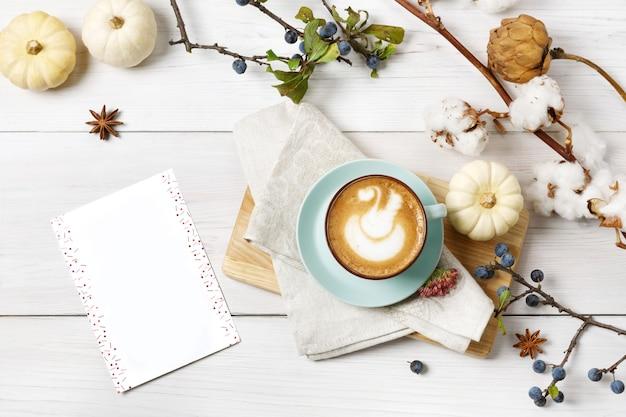 パンプキンスパイスラテ。泡、シナモンスティック、綿植物、小さな黄色のカボチャが入った青いコーヒーカップ。秋の秋のホットドリンク、カフェ、バーのコンセプト、トップビュー