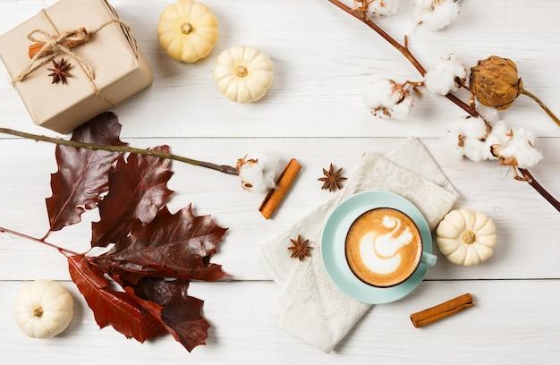 パンプキンスパイスラテ。泡、シナモンスティック、赤いカシの葉および小さい黄色のカボチャが付いているコーヒーカップ。秋の秋のホットドリンク、カフェ、バーのコンセプト、トップビュー