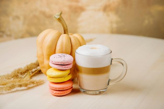 パンプキンスパイスラテ。カボチャ、マカロン、秋の装飾が施されたラテのカップ。クッキーと伝統的な秋のコーヒードリンク。
