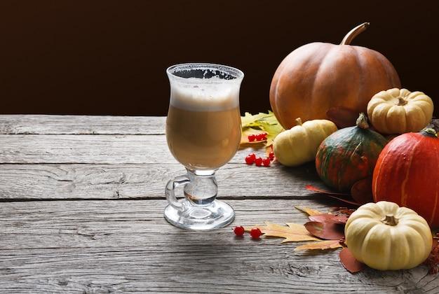 パンプキンスパイスラテ。クリーミーな泡、秋の乾燥した葉、素朴な木の小さなカボチャが入ったガラスのコーヒーカップ。秋のホットドリンク、季節のオファーのコンセプト