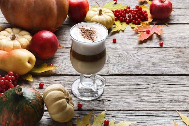 パンプキンスパイスラテ。クリーミーな泡、秋の乾燥した葉、リンゴ、素朴な木材で小さなカボチャとガラスのコーヒーカップ。秋のホットドリンク、季節のオファーのコンセプト