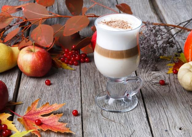 パンプキンスパイスラテ。クリーミーな泡、秋の乾燥した葉、リンゴ、素朴な木の小さな黄色のカボチャキューブが入ったガラスのコーヒーカップ。秋のホットドリンク、季節のオファーのコンセプト