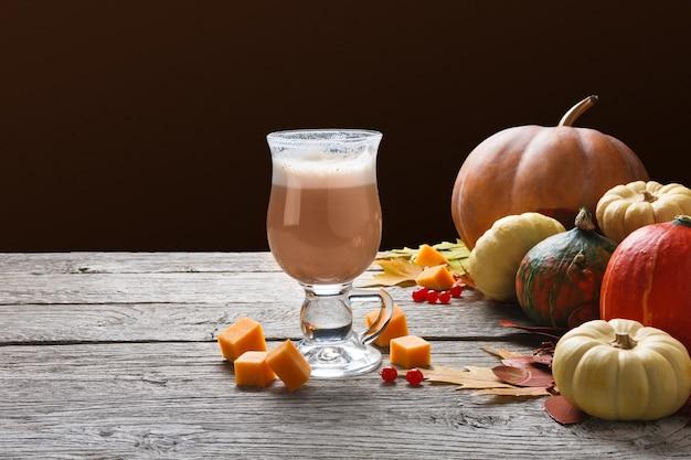パンプキンスパイスラテ。クリーミーな泡、秋の乾燥した葉、さいの目に切ったチーズ、素朴な木の小さなカボチャが入ったガラスのコーヒーカップ。秋のホットドリンク、季節のオファーのコンセプト