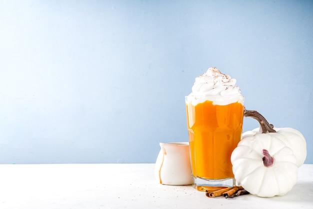 Латте или молочный коктейль из тыквенных специй, традиционный осенний горячий напиток с анисом, корицей и карамельной начинкой, на теплом фоне с небольшими декоративными тыквами и уютным свитером.