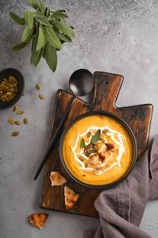 クリーミーな絹のような食感のカボチャの伝統的なスープで、セージの葉と赤唐辛子を黒いプレートまたはボウルに入れます。古い灰色の背景。スペースをコピーします。モックアップ。上面図、フラットレイ。