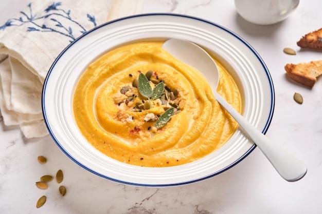 하얀 접시나 그릇에 세이지 잎과 고추를 넣은 크림 같은 부드러운 질감의 호박 전통 수프. 밝은 회색 배경. 공간을 복사합니다. 조롱. 평면도, 평면도.