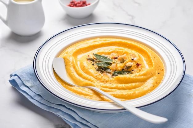 白いプレートまたはボウルにセージの葉と赤唐辛子を入れたクリーミーな絹のような食感のカボチャの伝統的なスープ。明るい灰色の背景。スペースをコピーします。モックアップ。上面図、フラットレイ。