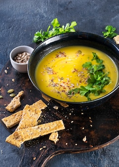 Pumpkin and vegetables cream soup with pumpkin seeds and parsley