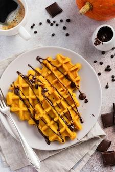 초콜렛과 설탕을 입힌 호박 와플이 가벼운 테이블과 오래된 소박한 아침 식사 테이블에서 아침 식사로 제공됩니다. 선택적 초점.