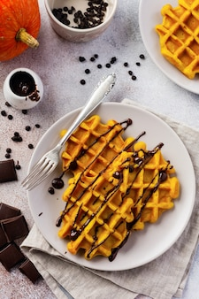 Pumpkin waffles with chocolate and icing sugar on light and old rustic breakfast table